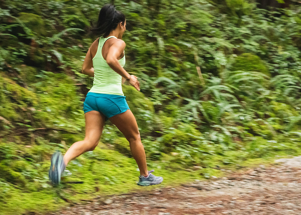Girl running along a path wearing blue short sblue trainers and a yellow top