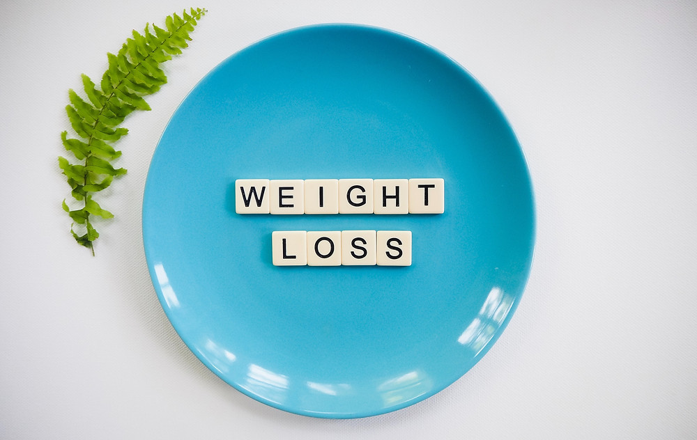Turquoise plate with scrabble tiles spelling weight loss