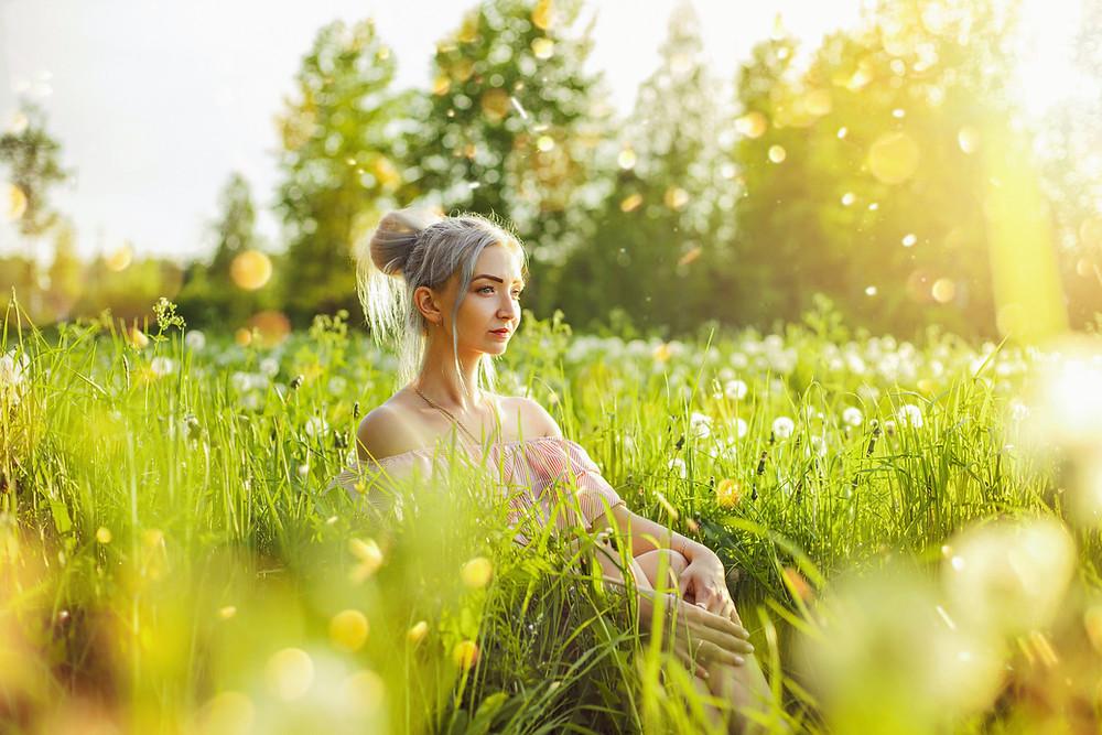 Woman sat in wildflower field in spring
