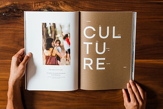 magazine open to culture page on wood table
