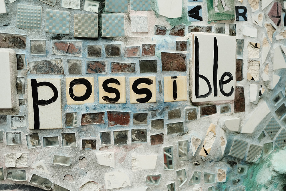 """Mosaic on a wall that says """"possible."""""""