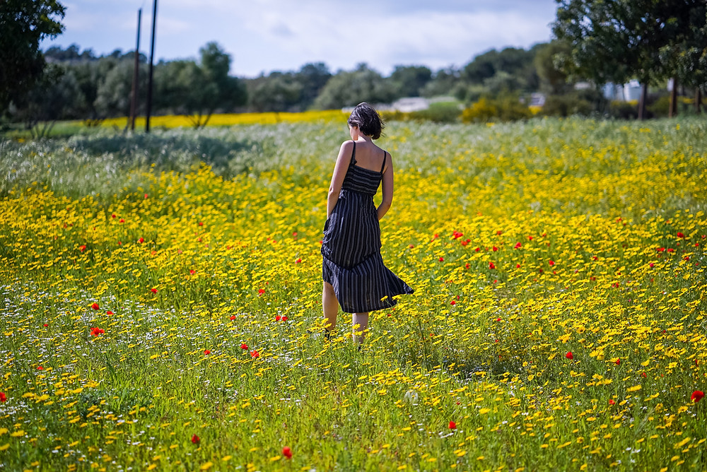 Woman walking through field of wildflowers with hands in pockets of her summer dress.