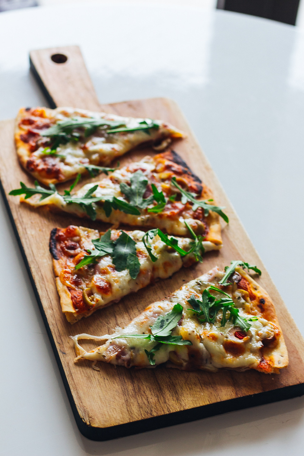 Four slices of vegetarian pizza on a cutting board