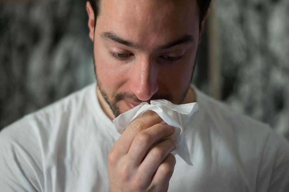 A man holding a tissue towards his nose.