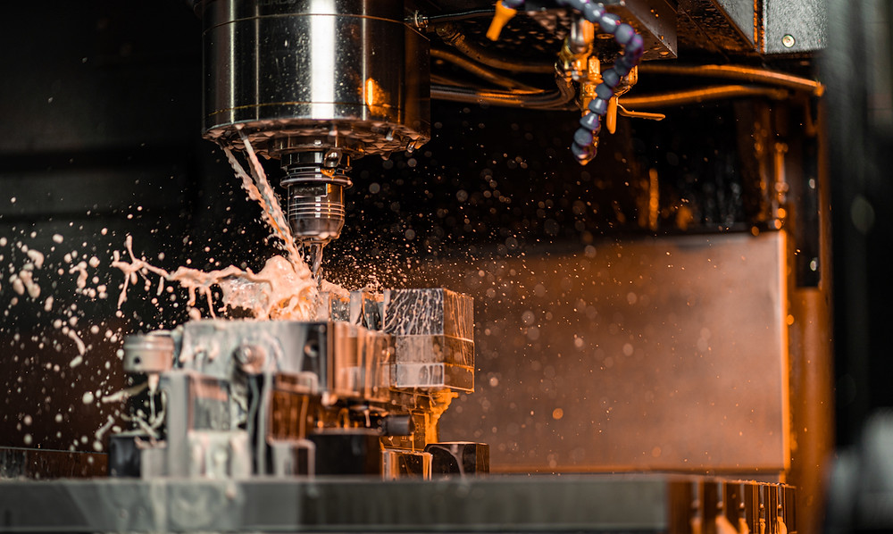 This is a picture of a CNC router, milling on a piece of metal, with coolant splattering away from the work.