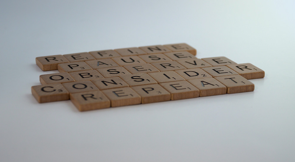 Scrabble tiles spelling out the words refine, pause, observe, consider, and repeat.