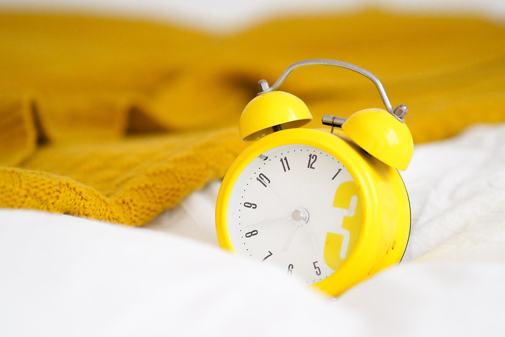 cute yellow alarm clock sitting on a bed with a wool blanket nearby