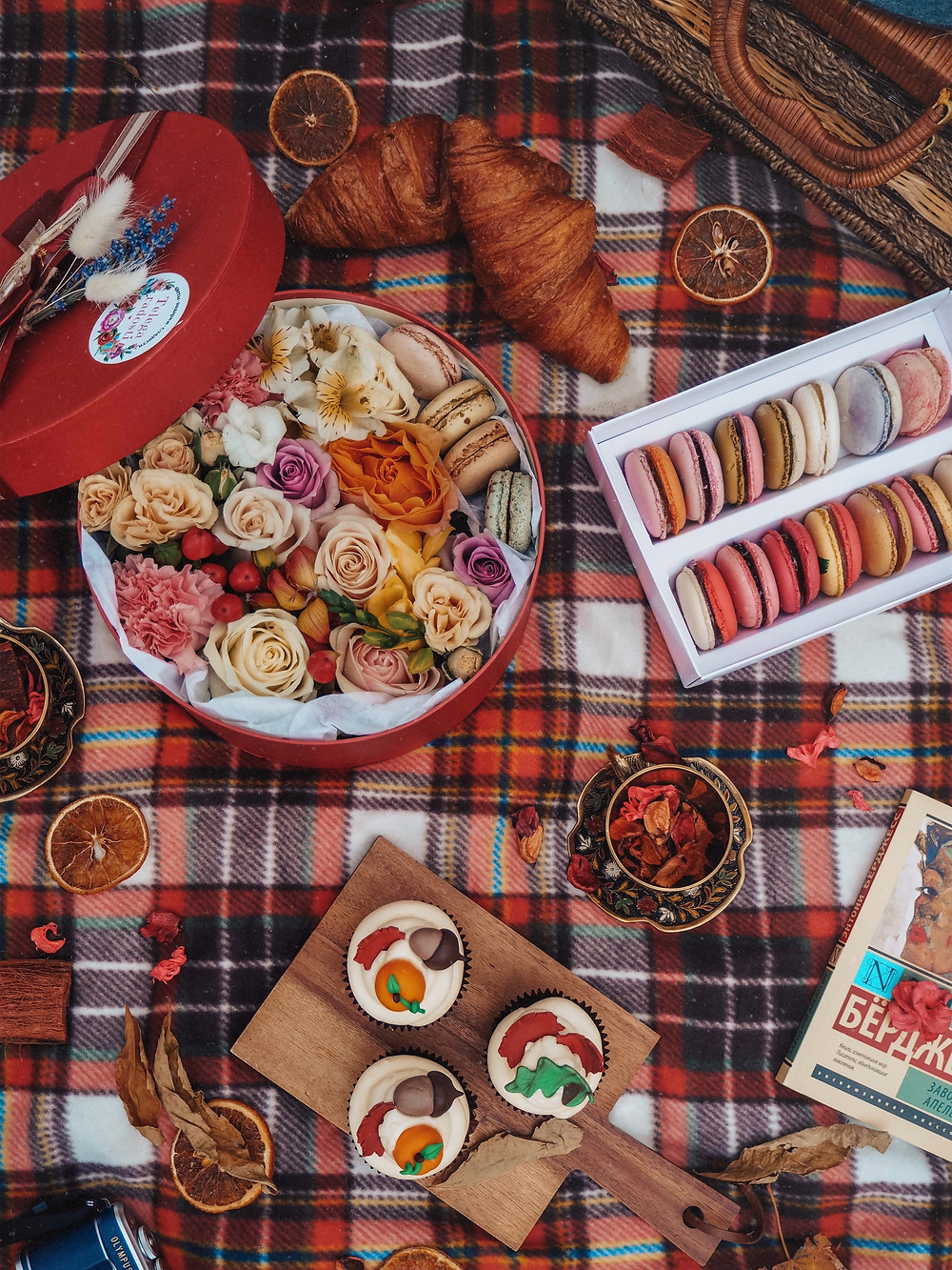 fall picnic with croisants, macarons, roses, fruit, basket