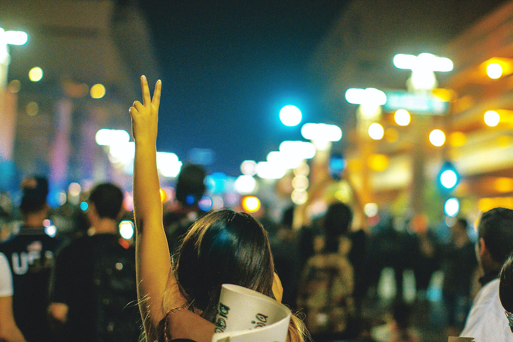 Crowd in bright city street at night, young adult with arm held high, raising index and middle fingers