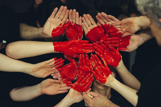 eight pairs on hands supporting each other and facing the camera plams out and painted to resemble a large red heart