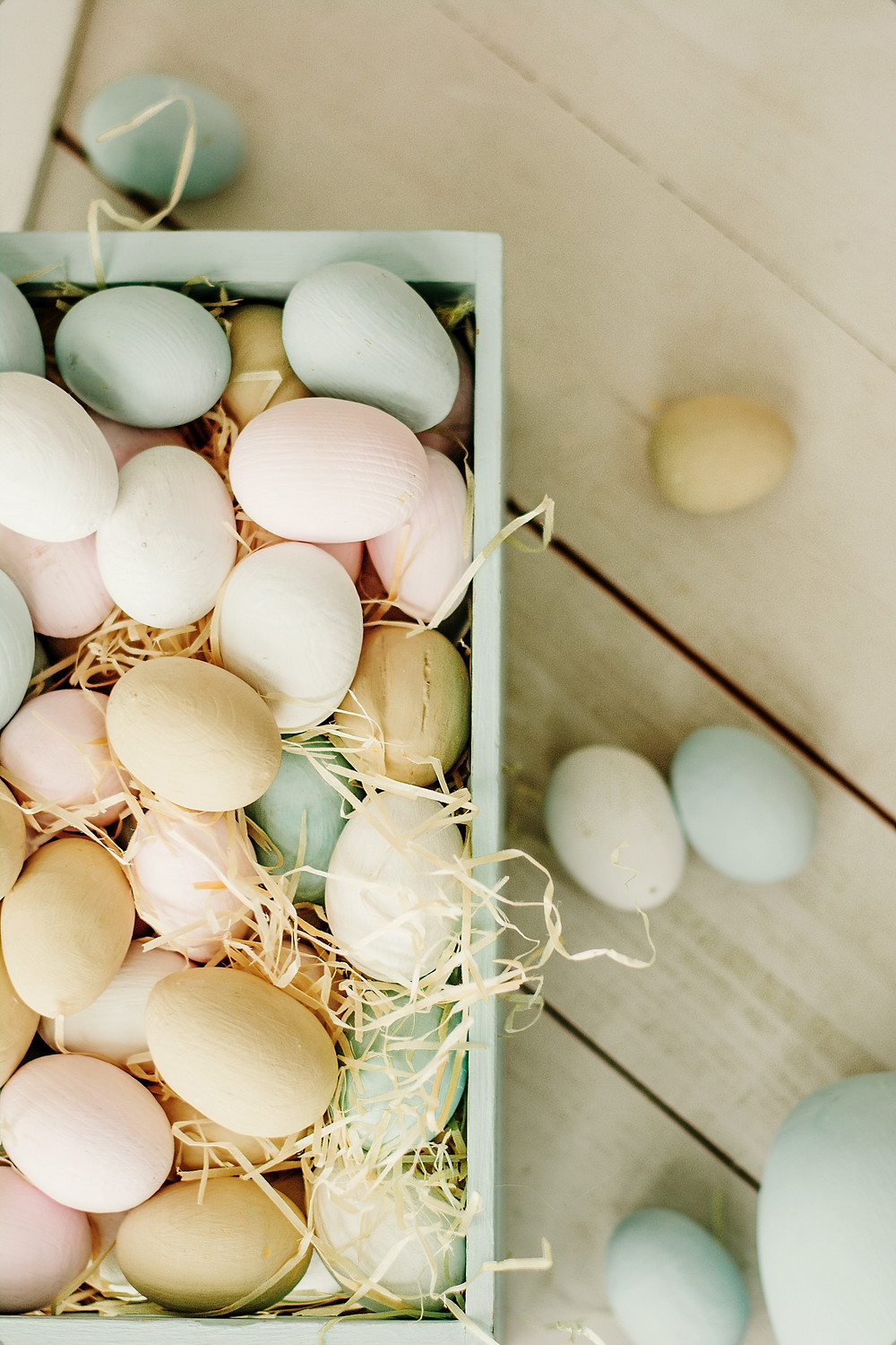 Aerial photo of pastel coloured eggs with straw in pastel blue box. Pastel coloured eggs scatted around outside of box
