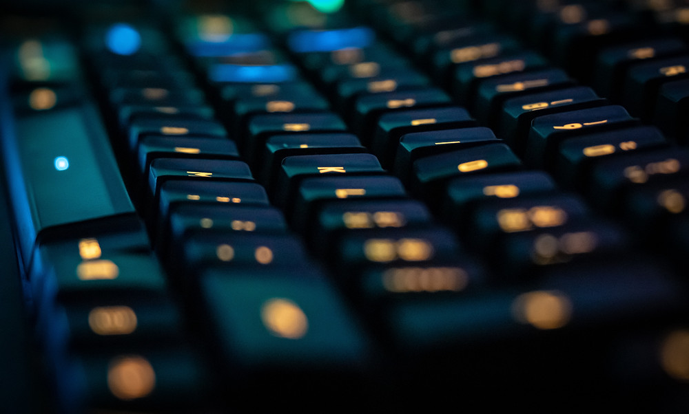 An image of a dark keyboard with illuminated yellow keys.