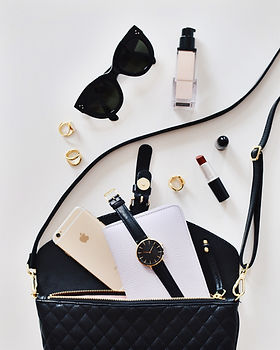 A display of accessories in a woman's purse, including lipsticks and other beauty products. | Glou Beauty