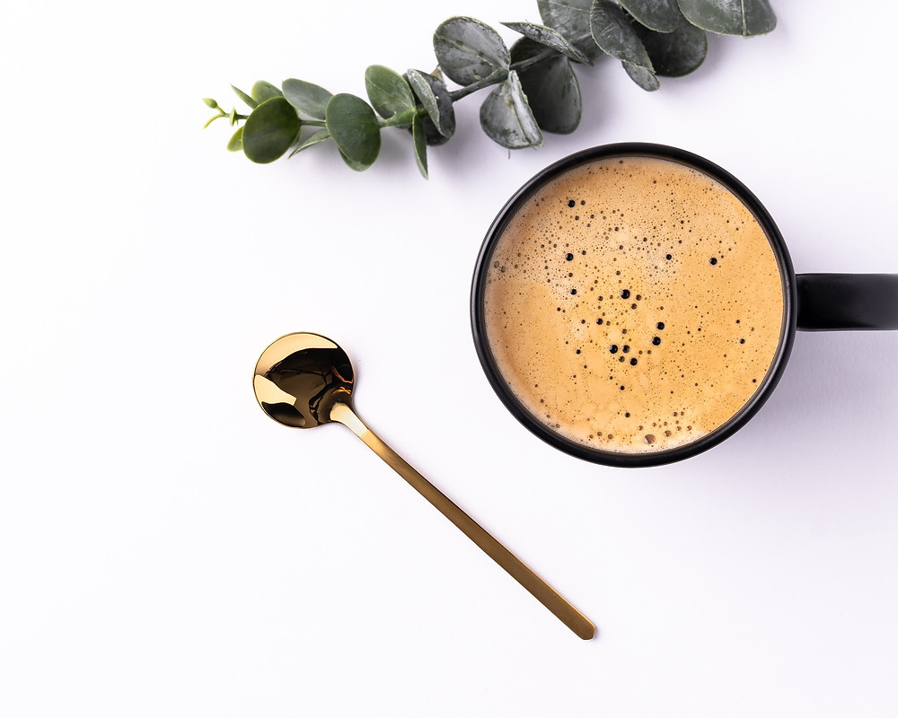 coffee cup beside gold spoon and eucalyptus leaf