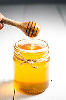 a wooden spoon above a glass jar of honey