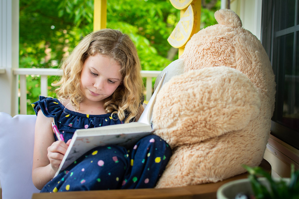 Girl wearing spotted dress, writing in a book or journal, with a giant teddy bear beside her