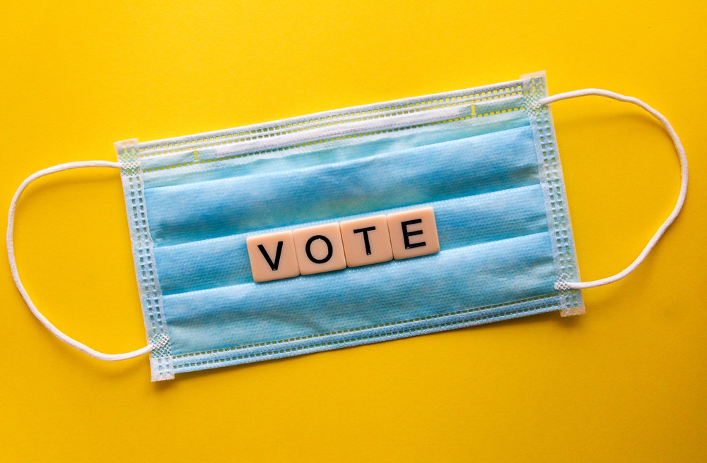 """A blue medical mask with the words """"vote"""""""