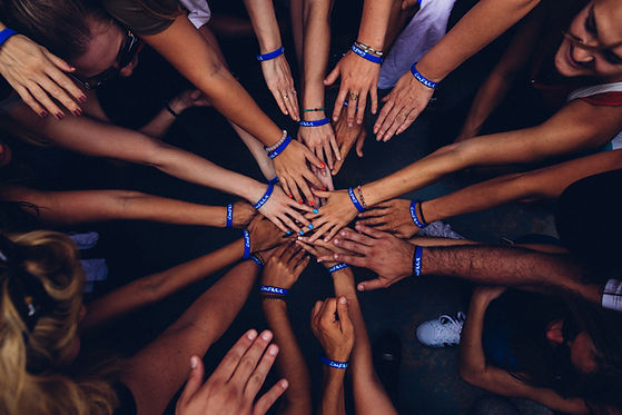 group of people with hand in a circle