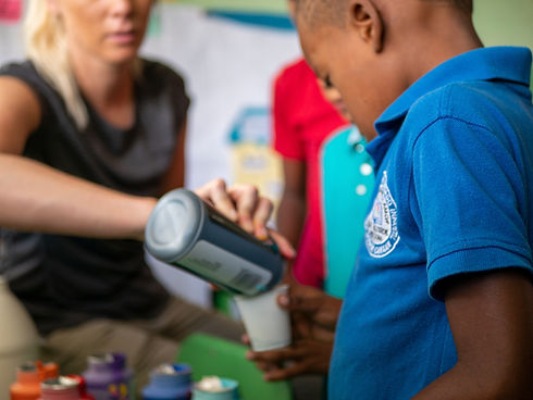 underpriveledged kids getting drink from a volunteer